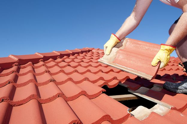 A roofer repairing titles on a roof
